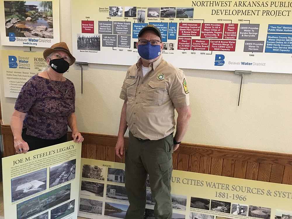 """Hobbs State Park-Conservation Area recently invited Beaver Water District to set up a """"Beaver Dam, Lake and Water District History"""" display in the Visitor Center at 20201 Arkansas 12 in Rogers. The installation was designed by Dot Neely, BWD education coordinator, and installed by Neely (left) and Chris Pistole, park interpreter. The installation may be viewed through May 31 during Visitor Center hours, 8 a.m. to 5 p.m. daily. Information: www.arkansasstateparks.com/parks/hobbs-state-park-conservation-area or www.bwdh2o.org.  (Courtesy Photo)"""