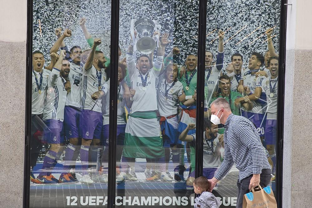 Un uomo e un ragazzo passano davanti a un poster del Real Madrid per la squadra che festeggia in un negozio di merchandising a Madrid, in Spagna, lunedì 19 aprile 2021. Il presidente UEFA Alexander Ceferin ha detto che i giocatori dei 12 club che creano la loro Super League potrebbero essere così Bandito dal Campionato Europeo quest'anno e dalla Coppa del Mondo il prossimo anno.  Ceferin ha parlato dopo una riunione del Comitato Esecutivo UEFA, che si è tenuta per poche ore, e club inglesi, italiani e spagnoli hanno annunciato il progetto che minaccia di dividere il calcio europeo.  (AP Photo / Paul White)