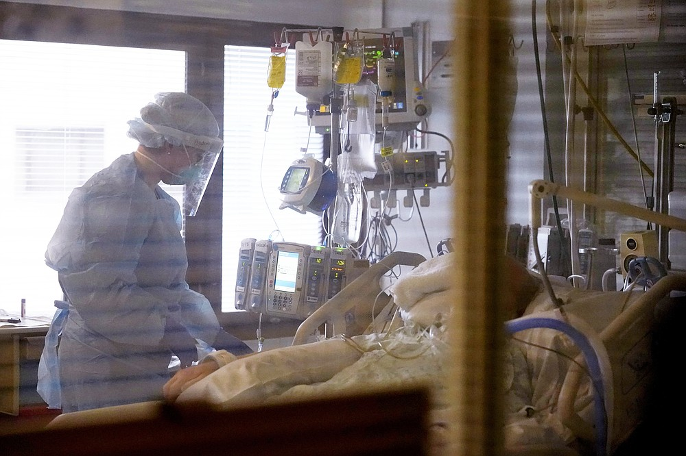 The Associated Press Registered nurse Andraya Zelle treats a patient in the COVID intensive care unit at UW Medical Center-Montlake in Seattle on Jan. 26.