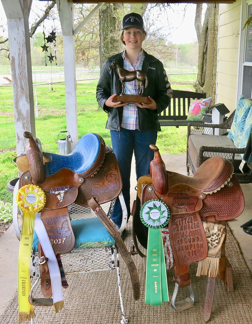 Westside Eagle Observer/SUSAN HOLLAND Landyn Perrine shows off some of the awards she has won in her rodeoing career, including trophy saddles for 2017 all-around champion in the Ozark Junior Rodeo Association and 2018 Little Wrangler all-around champion and ribbons won at the 2020 American Quarter Horse Association World Show in Oklahoma City. She is holding the bronze trophy she earned for placing third in the world in poles at the AQHA show.