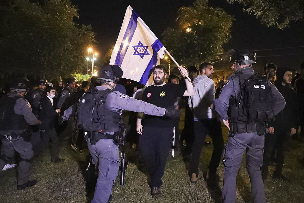 """Israeli border police block members of """"Lahava"""", a Jewish extremist group on approach to Damascus Gate to protest amid heightened tensions in the city, just outside Jerusalem's Old City, Thursday, April 22, 2021. (AP Photo/Ariel Schalit)"""