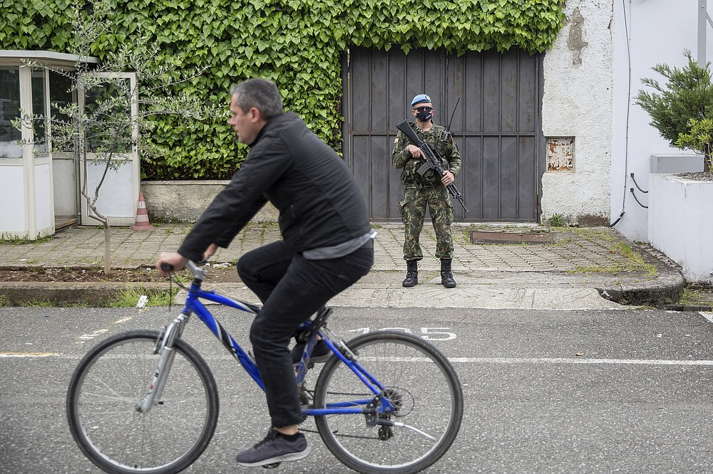 A man riding a bicycle passes beside a member of the Albanian army securing the Spanish embassy ahead of the general elections in Tirana, Saturday, April 24, 2021. Albania holds parliamentary elections on Sunday amid the virus pandemic and a bitter political rivalry between the country's two largest political parties but that will serve as a key milestone in the country's next step toward European Union membership. (AP Photo/Visar Kryeziu)