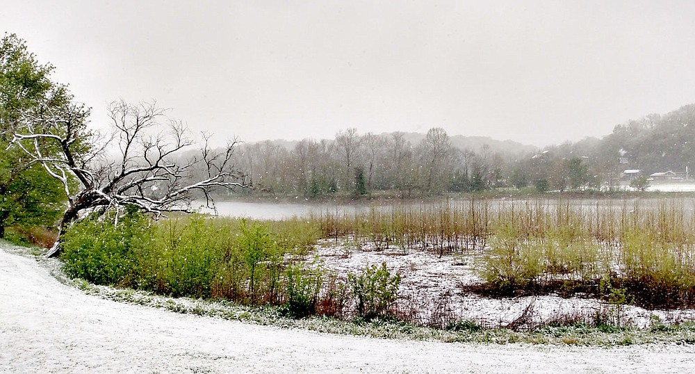 Keith Bryant/The Weekly Vista Lake Bella Vista sits surrounded by snow, with ongoing precipitation giving the appearance of fog during last week's unusual spring snowstorm.
