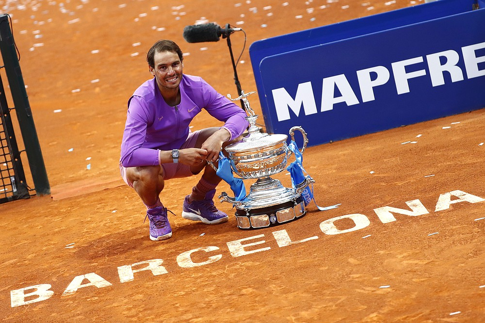 Rafael Nadal of Spain poses for a photo next to the trophy after winning the final Godo tennis tournament against Stefanos Tsitsipas of Greece in Barcelona, Spain, Sunday, April 25, 2021. Nadal won by 6-4, 6-7, 7-5 (AP Photo/Joan Monfort)