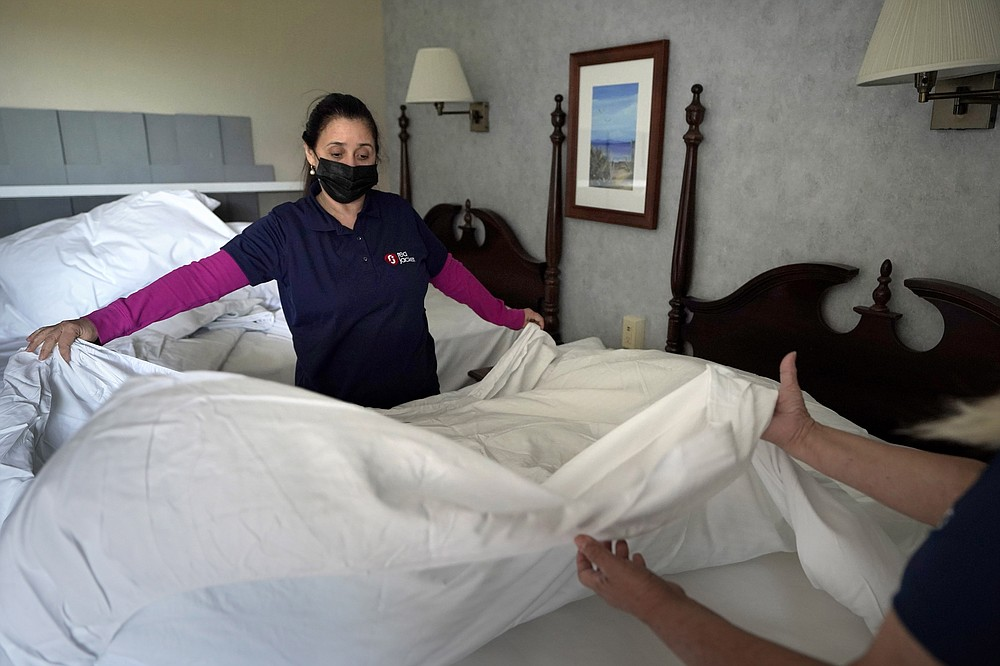 Workers Miriam Mattos, left, and Marilene Souto, hands only at right, both of Hyannis, Mass., make a bed, Tuesday, April 6, 2021, at Red Jacket Resorts, in Yarmouth, Mass. Hotels, restaurants and other businesses in tourist destinations are warning that hiring challenges during the coronavirus pandemic could force them to pare back operating hours or curtail services just as they're eyeing a bounce-back summer.  (AP Photo/Steven Senne)