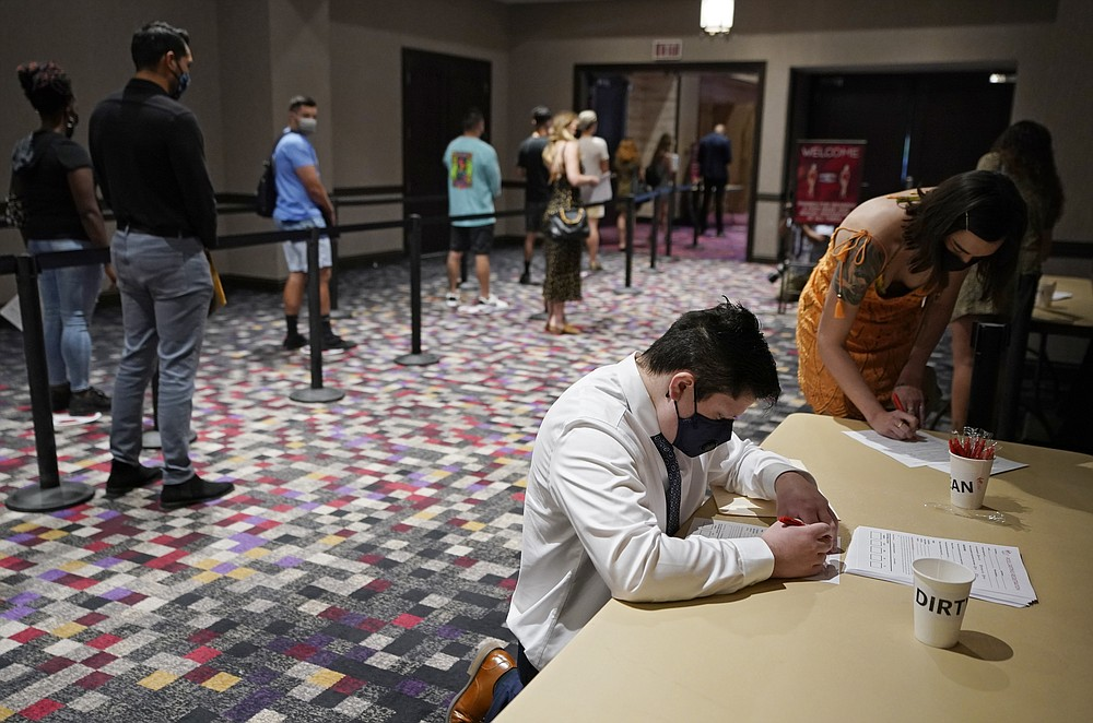 FILE - In this April 22, 2021, file photo, people wait in line to apply for seasonal jobs at Virgin Hotels Las Vegas in Las Vegas. The hotel-casino, which opened in March, held the casting call to hire for seasonal positions at the resort pool and dayclub. Hotels, restaurants and other businesses in tourist destinations are warning that hiring challenges during the coronavirus pandemic could force them to pare back operating hours or curtail services just as they're eyeing a bounce-back summer. (AP Photo/John Locher, File)