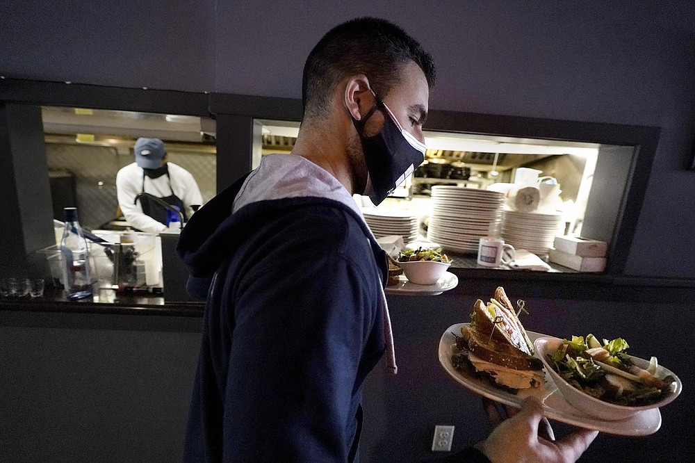 Bartender Denis Angelov, of Provincetown, Mass., left, carries plates of food from the kitchen, behind, at Tin Pan Alley restaurant, Tuesday, April 6, 2021, in Provincetown. Hotels, restaurants and other businesses in tourist destinations are warning that hiring challenges during the coronavirus pandemic could force them to pare back operating hours or curtail services just as they're eyeing a bounce-back summer. (AP Photo/Steven Senne)