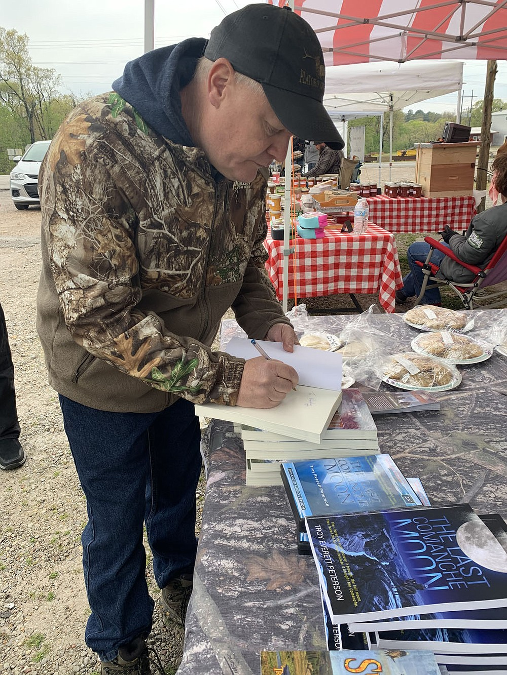 SALLY CARROLL/SPECIAL TO MCDONALD COUNTY PRESS Author Troy Everett Peterson signs a book for a customer at a recent Farmers Market event at Sim's Corner. Peterson's books also are available online on Amazon and Barnes & Noble.