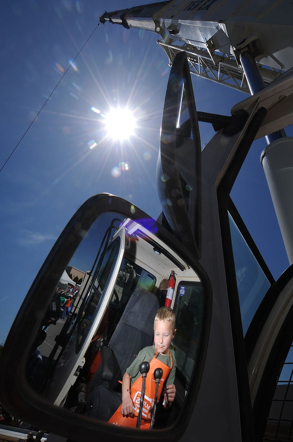 STAFF PHOTO BEN GOFF -- 05/03/14 - Aaron Fletcher, 5, of Rogers, explores the controls of a Nabholz 60-Ton Terex crane, as reflected in one of the crane's rear-view mirrors, during the 8th Annual Junior League of Northwest Arkansas Touch a Truck event at Pinnacle Hills Promenade mall in Rogers on Saturday May 3, 2014.