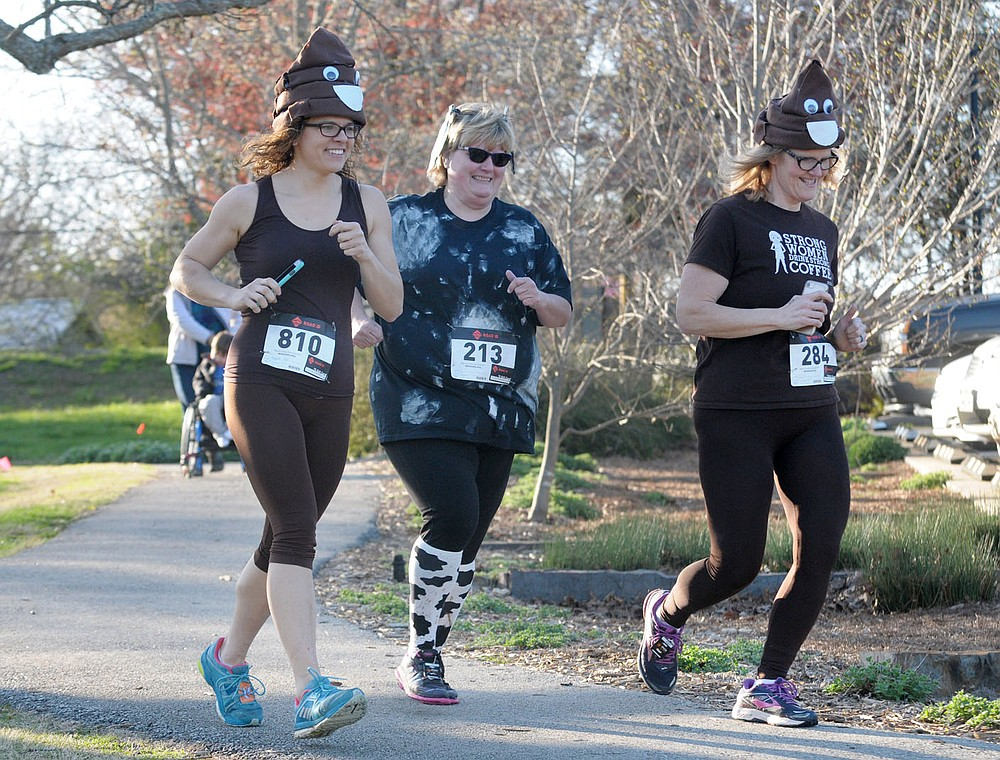 NWA Democrat-Gazette/DAVID GOTTSCHALK Kim Pilgrim (from left), Felecia Stark and Terry King participate Friday, March 30, 2018, in the 2018 Cow Paddy 5K at Gulley Park in Fayetteville. The annual 5K and 1K Fun Run supports health and fitness education in Fayetteville Public Schools, the Fayetteville Public Education Foundation, and The Spark Foundation's growing outreach programming. The run also included a Best Dressed Cow and Craziest Running Costume contest.