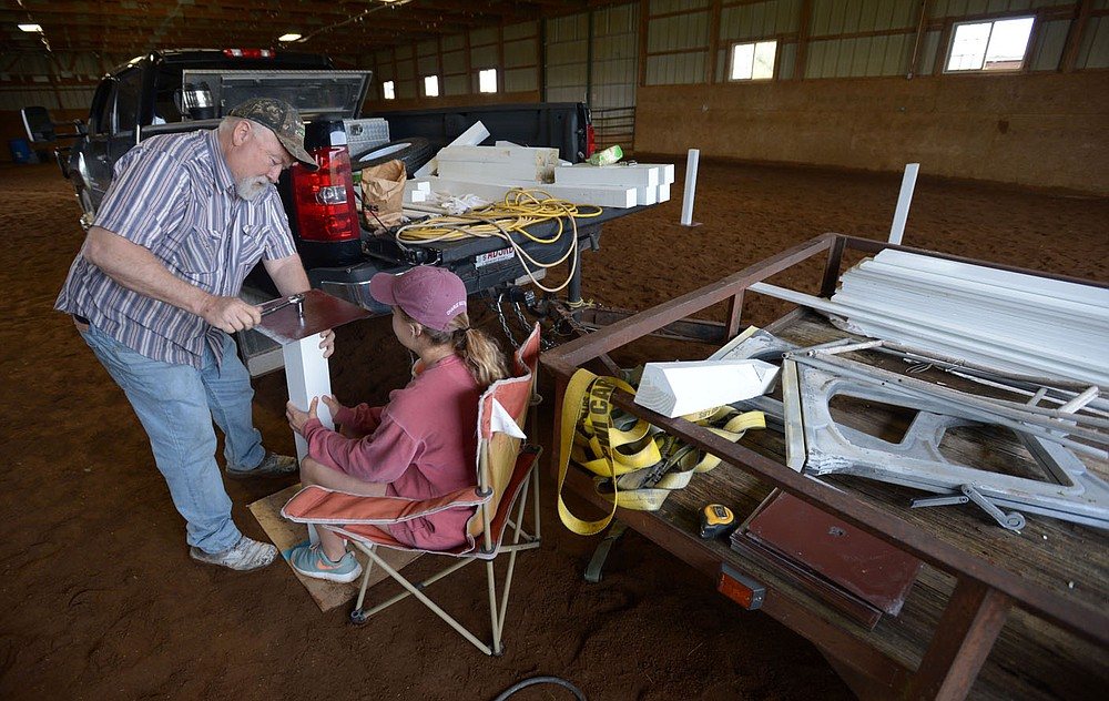 NWA Democrat-Gazette/ANDY SHUPE David Helm, equine specialist and chief safety officer for Equestrian Bridges, works with volunteer Isabella Balas, a University of Arkansas student from Little Rock, Friday, May 4, 2018, while setting up for the sixth annual Mini Derby at Parkerman Stables in Fayetteville. The miniature horse derby and watch party for today's 144th Kentucky Derby serves as a fundraiser for Equestrian Bridges which offers equine therapy to build social and communication skills in children with those deficits.