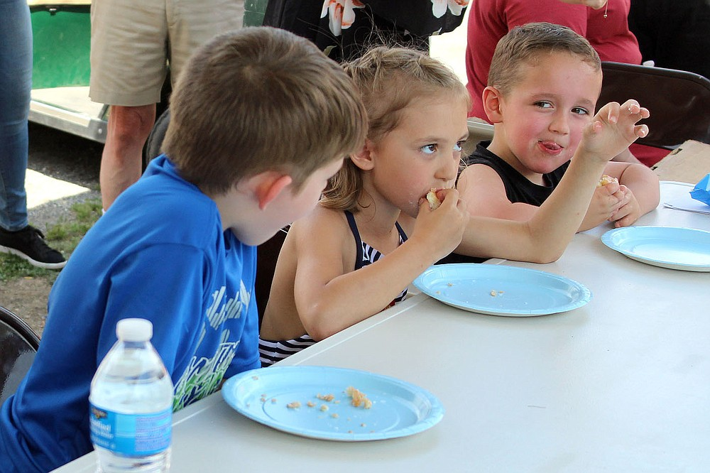 MEGAN DAVIS/MCDONALD COUNTY PRESS Rival competitors survey Isabelle Wittenmeyer as she intently finishes her donut and claims victory during the 2019 Donut Eating Contest. Wittenmeyer finished her donut in 1 minute, 30 seconds.