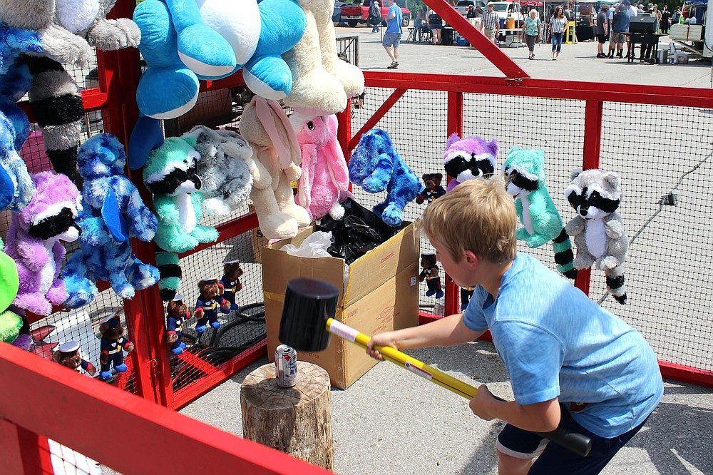 MEGAN DAVIS/MCDONALD COUNTY PRESS A young boy takes his chance at one of the game booths, attempting to smash a can with a heavy mallet in hopes of taking home a prize.