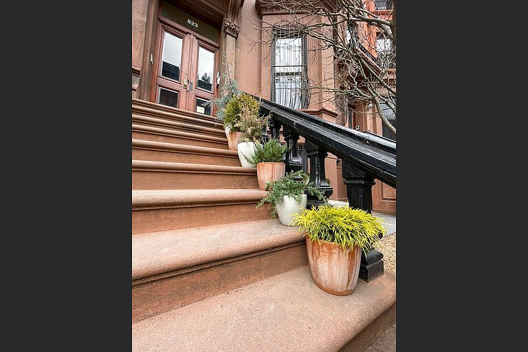 A procession of conifers in sturdy pots provide a welcoming guide up the stairs to the stoop of this brownstone in the Brooklyn borough of New York. (Kate Cook via AP)