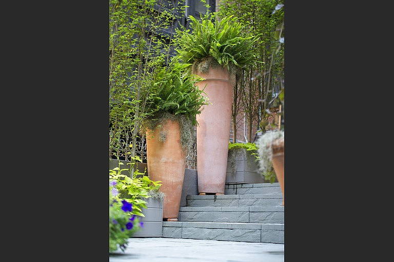 Tall terra cotta planters add a 'wow' factor to this stoop, with landscaping design by Janice Parker. (Neil Landino Jr./Janice Parker Landscape Architects via AP)