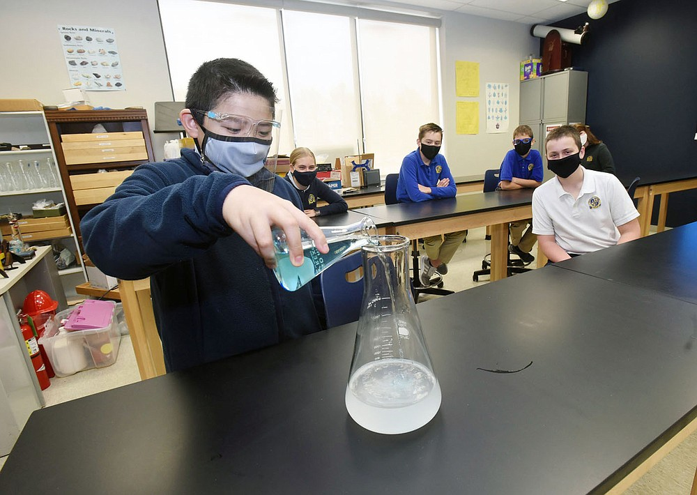 Preston Vo, a student at Haas Hall Academy Bentonville, demonstrates a chemical reaction by mixing solutions in teacher Pete Golden's chemistry classroom at the campus. Go to nwaonline.com/210428Daily/to see more photos. (NWA Democrat-Gazette/Flip Putthoff)