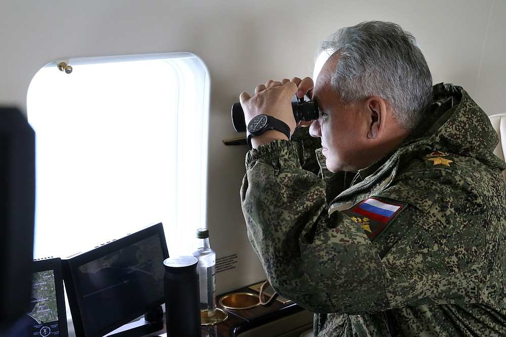 This handout photo released on Thursday, April 22, 2021 by the Russian Defense Ministry Press Service shows, Russian Defense Minister Sergei Shoigu watches drills form a board of military helicopter in Crimea. The Russian military is conducting massive drills in Crimea involving dozens of navy ships and thousands of troops in a show of force amid tensions with Ukraine. The maneuvers were described as the largest since Russia annexed Ukraine's Black Sea peninsula in 2014 and threw its weight behind separatist insurgents in eastern Ukraine. (Vadim Savitsky/Russian Defense Ministry Press Service via AP)