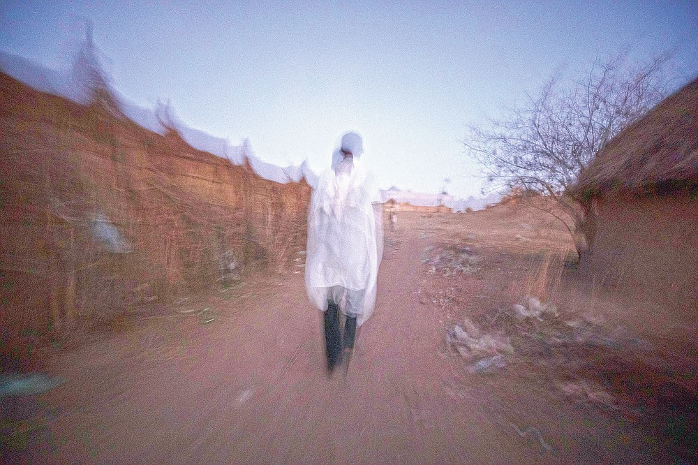 """Tigrayan refugee Abraha Kinfe Gebremariam, 40, walks back to his shelter after praying at a church early in the morning in Hamdayet, eastern Sudan, near the border with Ethiopia, on March 21, 2021. As his family crossed the Tekeze River, leaving the Tigray bloodshed behind, he felt the burden of the previous month ease. """"I was 100% sure the babies would grow up, that things would change from that moment,"""" he said. """"Somehow my stress melted away. There were no more fears for our lives."""" (AP Photo/Nariman El-Mofty)"""