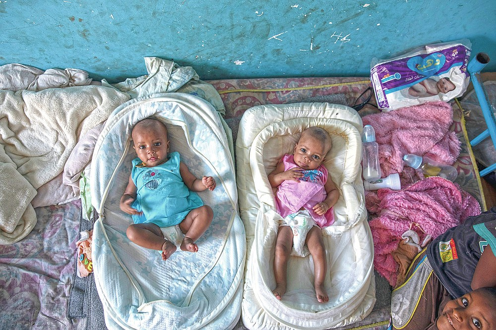 """Tigrayan 4-month-old twin sisters Aden, left, and Turfu Gebremariam, lie together inside their family's shelter in Hamdayet, eastern Sudan, near the border with Ethiopia, on March 21, 2021. In the fear and despair of the days following their birth, the twins were left unnamed. There was simply no time. Finally, their young brother, Micheale, christened them himself. One of the girls was named Aden, or """"paradise."""" The other, who reminds people of her mother, was named Turfu, or """"left behind."""" (AP Photo/Nariman El-Mofty)"""