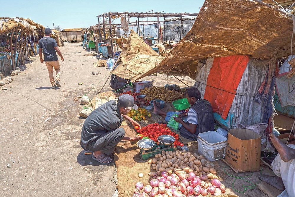 Tigrayan refugee Abraha Kinfe Gebremariam, 40, buys tomatoes at the market in Hamdayet, eastern Sudan, near the border with Ethiopia, on March 21, 2021. One day during the conflict in his home village, his son, Daniel, tried to visit the market and saw some 10 bodies being piled onto a vehicle for burial. He saw another four bodies in the dirt. Daniel never went to the market again. (AP Photo/Nariman El-Mofty)