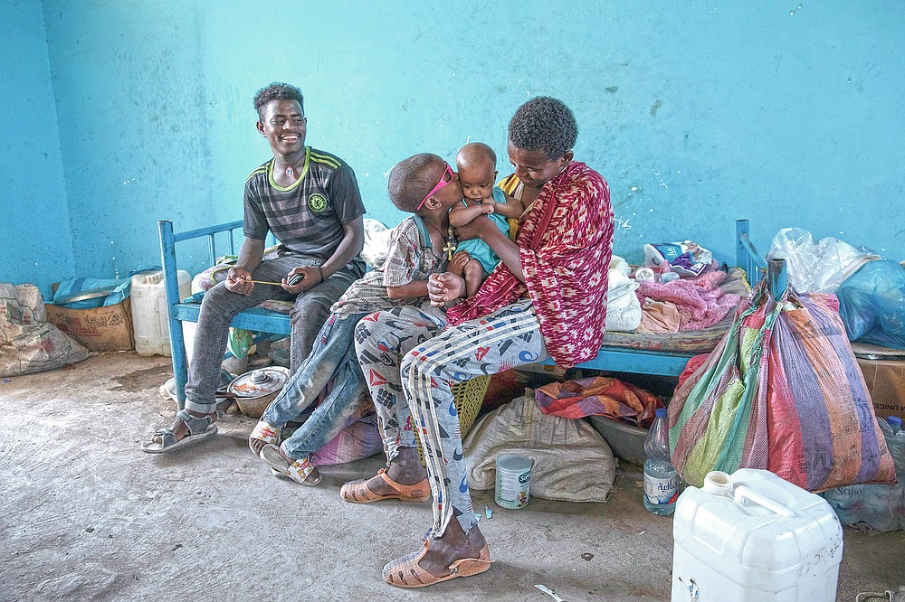Tigrayan 5-year-old refugee Micheale Gebremariam kisses his 4-month-old sister, Aden, as his 19-year-old uncle, Goytom Tsegay, left, sits with them, inside their family's shelter in Hamdayet, eastern Sudan, near the border with Ethiopia, on March 21, 2021. (AP Photo/Nariman El-Mofty)