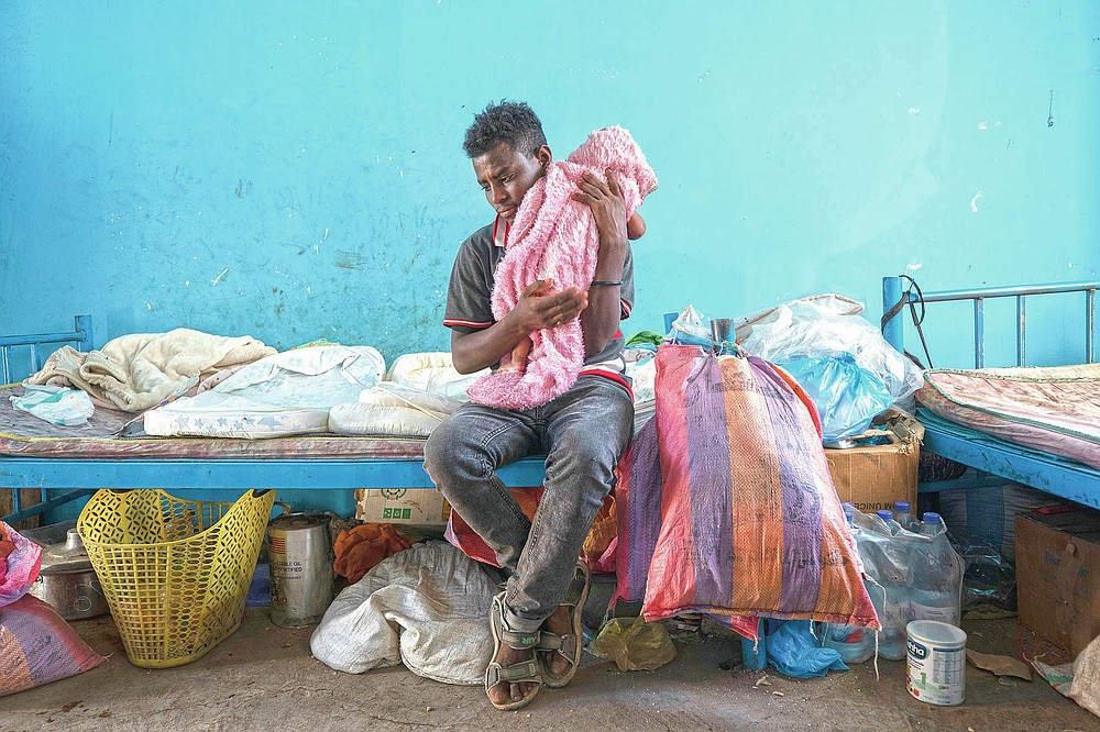 """Tigrayan 19-year-old refugee Goytom Tsegay, tries to comfort his 4-month-old niece, Turfu Gebremariam, inside their family's shelter in Hamdayet, eastern Sudan, near the border with Ethiopia, on March 21, 2021. """"I spend the whole day with them. ... My favorite part is feeding them. I've decided to stay with them all their lives."""" (AP Photo/Nariman El-Mofty)"""