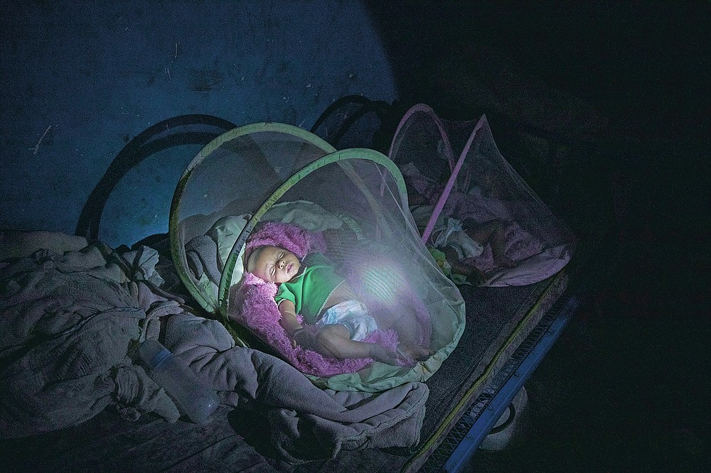 Tigrayan refugee Abraha Kinfe Gebremariam, 40, uses a flashlight to check on his 4-month-old twin daughters, Aden and Turfu, after praying at a church early in the morning, in Hamdayet, eastern Sudan, near the border with Ethiopia, on March 21, 2021. Even as Tigrayans ran for their lives or jostled for space on a boat to safety, the sight of the tall, silent, sorrowful man carrying the tiny twin girls made people pause. (AP Photo/Nariman El-Mofty)