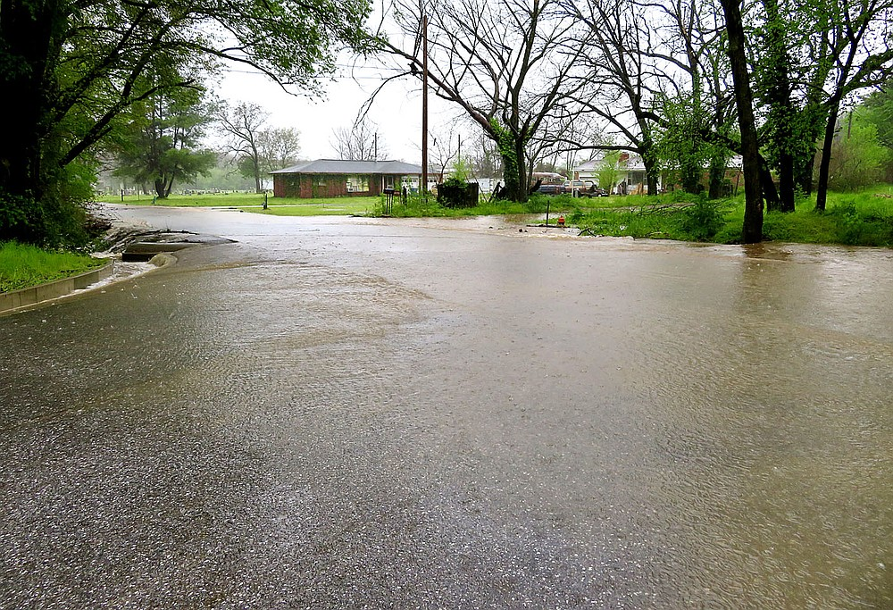Westside Eagle Observer/RANDY MOLL Water overflowed the roadway at the junction of Pioneer Lane with Marion Lee Road in Gentry on Wednesday morning following heavy rains which fell overnight and into the morning hours.