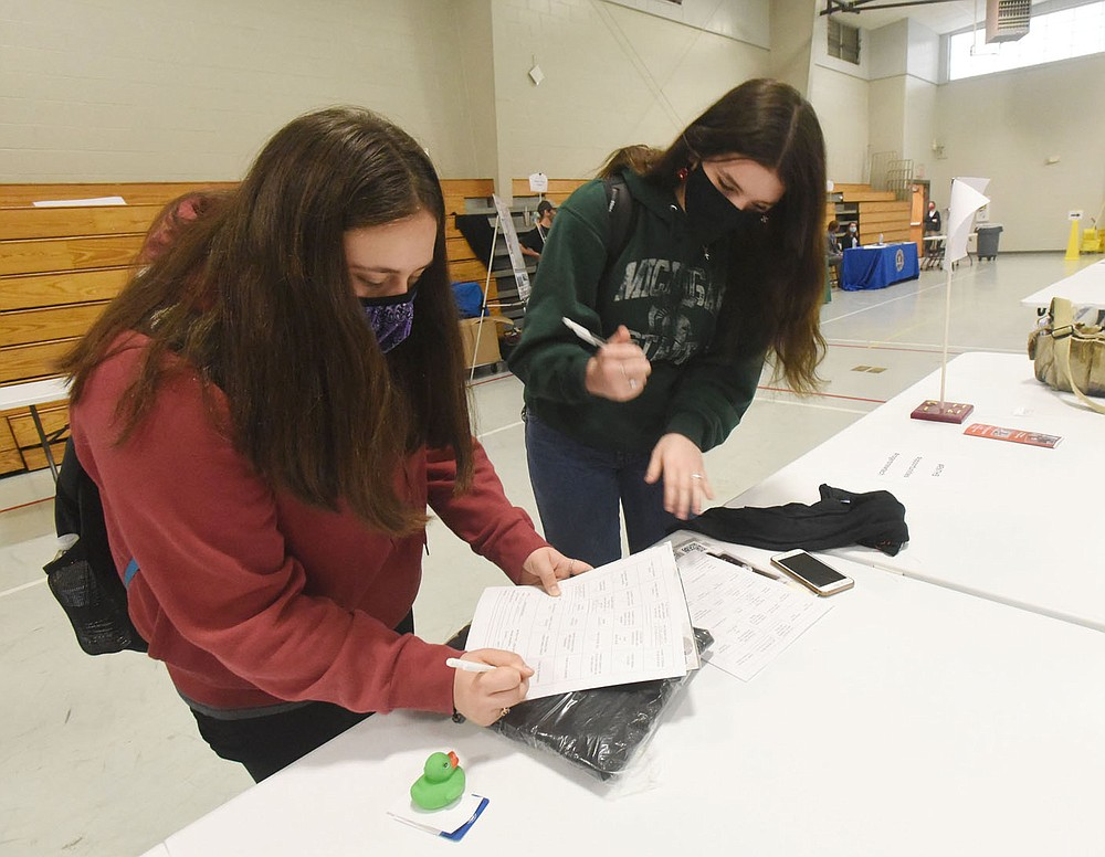 Students Brittany Schade (left) and Lillian Lake fill out forms on Wednesday April 28 2021 at the Rogers New Technology High School internship fair. Go to nwaonline.com/210428Daily/ to see more photos. (NWA Democrat-Gazette/Flip Putthoff)