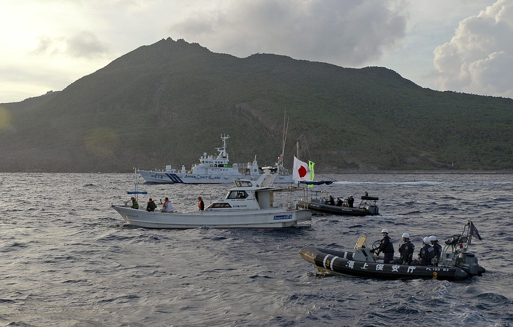 FILE - In this Sunday, Aug. 18, 2013, file photo, a Japanese Coast Guard boat and vessel sail alongside Japanese activists' fishing boat, not in photo, warning the activists away from a group of disputed islands called Senkaku by Japan and Diaoyu by China. Japan on Wednesday, April 28, 2021, said its military has raised caution levels around the Senkaku islands that it controls but are also claimed by Beijing after six Chinese warships passed near the area and a reconnaissance helicopter flew toward it. (AP Photo/Emily Wang, File)