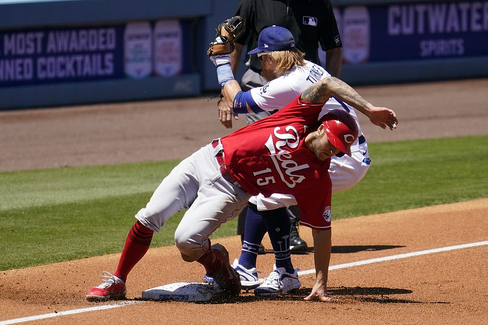 Cincinnati Reds' Nick Senzel (15) is tagged out at third base by Los Angeles Dodgers third baseman Justin Turner on a steal attempt during the first inning of a baseball game Wednesday, April 28, 2021, in Los Angeles. (AP Photo/Marcio Jose Sanchez)