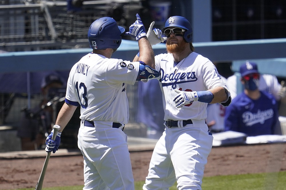 Los Angeles Dodgers' Justin Turner, right, celebrates his solo home run with Max Muncy during the third inning of a baseball game against the Cincinnati Reds Wednesday, April 28, 2021, in Los Angeles. (AP Photo/Marcio Jose Sanchez)