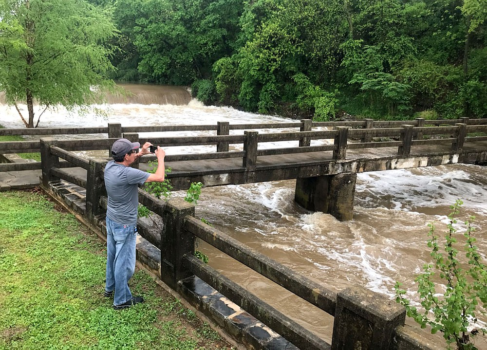 Janelle Jessen/Siloam Sunday John Christie takes a picture of floodwaters in Sager Creek on Wednesday afternoon.