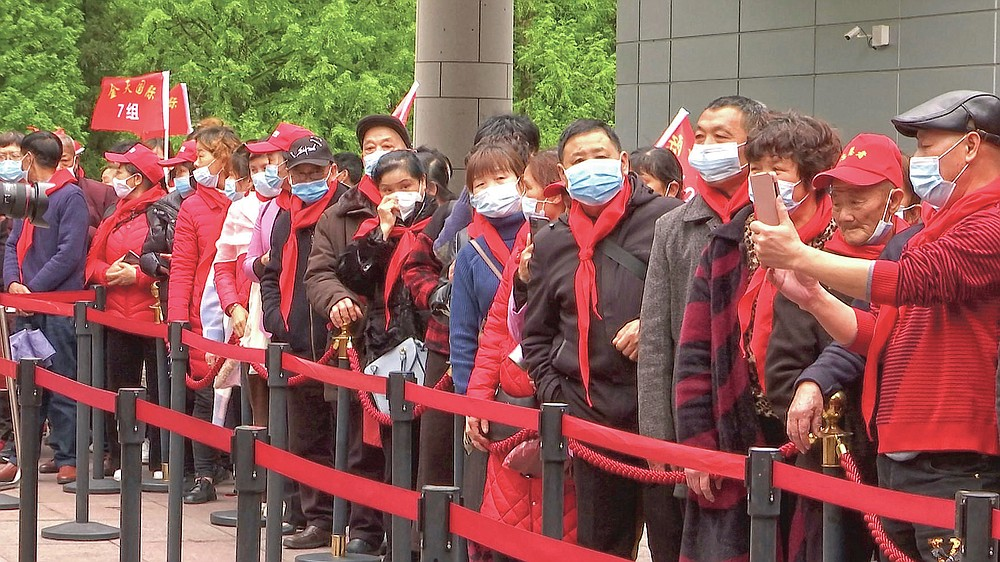 Tourist groups stand in line to enter the Jinggangshan Revolution Museum in Jinggangshan in southeastern China's Jiangxi province, on April 8, 2021. On the hundredth anniversary of the Chinese Communist Party, tourists in China are flocking to historic sites and making pilgrimages to party landmarks. (AP Photo/Emily Wang)