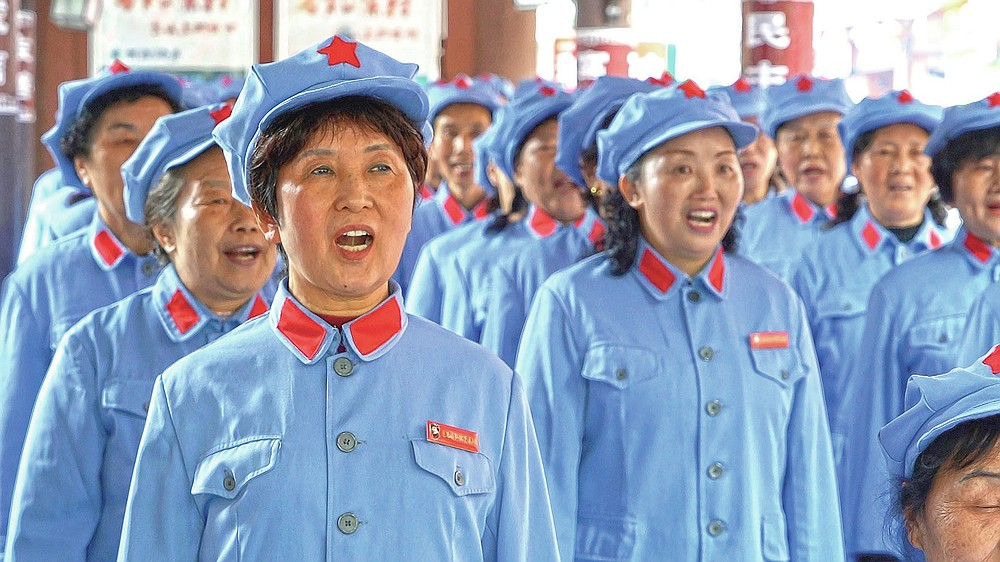 A group of local retirees gather to sing Red Army revolutionary songs in the city of Zunyi in Southwestern China's Guizhou province on April 12, 2021. The group, whose members' ages range from their late 50s to over 80, gather regularly to sing to tourists visiting the nearby Zunyi Memorial Museum. The museum, located at the site of the Zunyi Conference, was where the late Communist leader Mao Zedong rose to power. (AP Photo/Emily Wang)