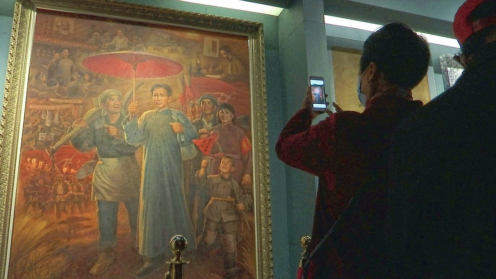 A tourist takes photos of a painting depicting the late Communist leader Mao Zedong, at the Jinggangshan Revolution Museum in Jinggangshan in southeastern China's Jiangxi province, on April 8, 2021. On the hundredth anniversary of the Chinese Communist Party, tourists in China are flocking to historic sites and making pilgrimages to party landmarks. (AP Photo/Emily Wang)