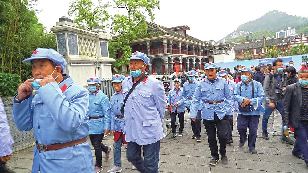 Tourists from the southern Henan province wear Red Army uniforms as they walk towards the Zunyi Memorial Museum in the city of Zunyi in Southwestern China's Guizhou province on April 12, 2021. The museum, located at the site of the Zunyi Conference, was where the late Communist leader Mao Zedong rose to power. (AP Photo/Emily Wang)