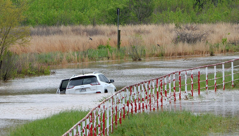 A car sits abandoned Thursday in deep water along Dead Horse Mountain Road in Fayetteville. Heavy rain over Wednesday and Thursday have swollen the White River outside of its banks, causing the road to flood. (NWA Democrat-Gazette/Andy Shupe)