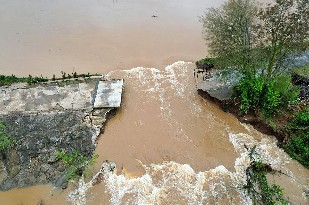 A section of the dam that creates Lake Bella Vista is seen washed away from Wednesday's storms. The break is in a section of the dam between to concrete overflow. The main dam gate and over flows became blocked by debris created during the storm.  Check out nwaonline.com/210430Daily/ for today's photo gallery.  (NWA Democrat-Gazette/Spencer Tirey)