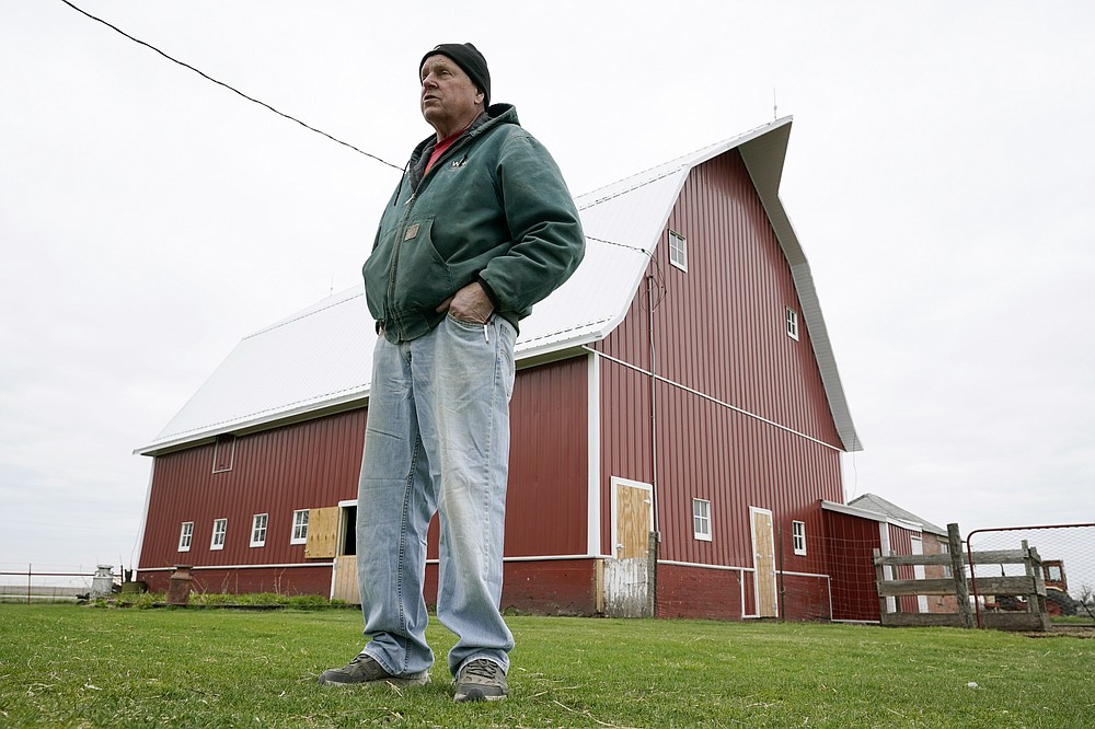 CORRECTS YEARS OF FARMING TO 43 INSTEAD OF 45 - Morey Hill stands near a barn on his farm, Friday, April 16, 2021, near Madrid, Iowa. In 43 years of farming, Hill had seen crop-destroying weather, rock-bottom prices, trade fights and surges in government aid, but not until last year had he endured it all in one season. Now, as Hill and other farmers begin planting the nation's dominant crops of corn and soybeans, they're dealing with another shift _ the strongest prices in years and a chance to put much of the recent stomach-churning uncertainty behind them. (AP Photo/Charlie Neibergall)