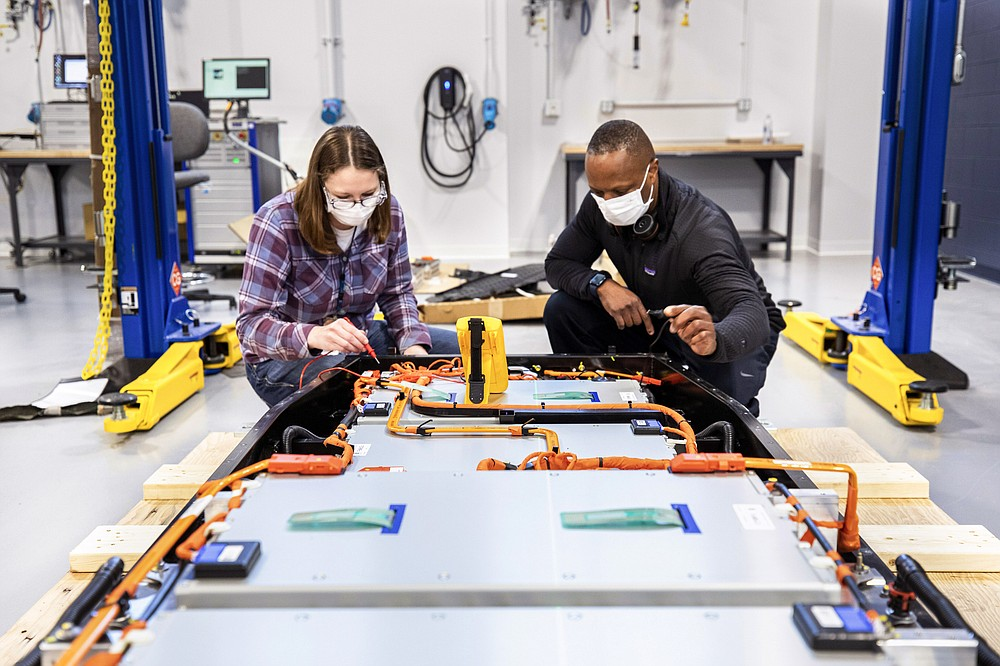This photo provided by Ford shows Dane Hardware, Ford Motor Co. design and release engineer, and Mary Fredrick, Ford Motor Co. battery validation engineer, measure the voltage of a battery using a digital multi-meter at Ford's Battery Benchmarking and Test Laboratory in Allen Park, Mich., on April 6, 2021. (Ford via AP)