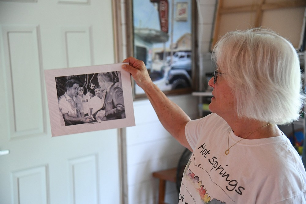 Local artist Tansill Stough-Anthony shows a print of a painting she did of President Kennedy meeting a young Bill Clinton. - Photo by Tanner Newton of The Sentinel-Record