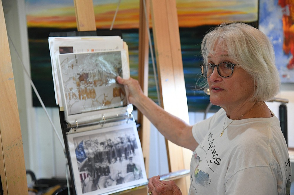 Local artist Tansill Stough-Anthony shows a print of one of her JFK paintings. - Photo by Tanner Newton of The Sentinel-Record