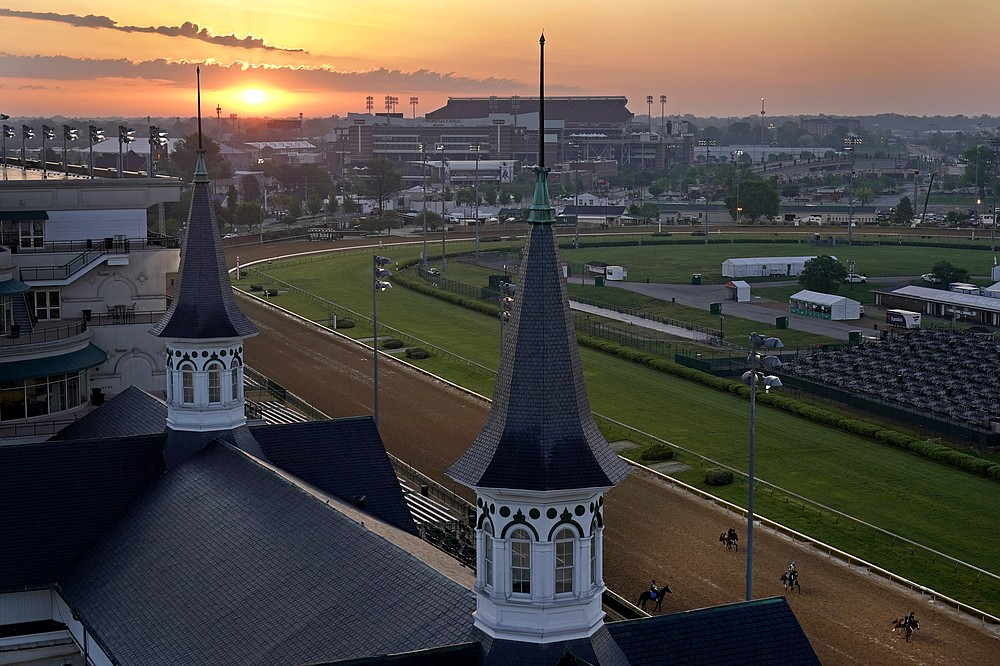 Horses work out as the sun rises at Churchill Downs Friday, April 30, 2021, in Louisville, Ky. The 147th running of the Kentucky Derby is scheduled for Saturday, May 1. (AP Photo/Charlie Riedel)