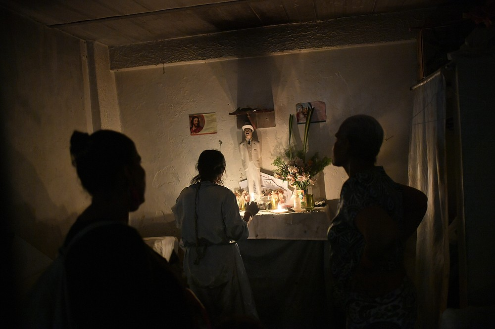 """People stand before an altar featuring a statue of the late, Venezuelan Dr. Jose Gregorio Hernandez on the day of his beatification ceremony by the Catholic church, inside a residence in Caracas, Venezuela, Friday, April 30, 2021. Known as the """"doctor of the poor,"""" Hernandez is being beatified, a step towards sainthood. (AP Photo/Matias Delacroix)"""