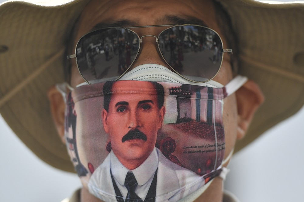 """A man wears a mask featuring the image of the late, Venezuelan Dr. Jose Gregorio Hernandez, on the day of his Beatification ceremony outside the church that guards his remains in La Candelaria area of Caracas, Venezuela, Friday, April 30, 2021. Known as the """"doctor of the poor, Hernandez will be beatified Friday by the Catholic church, a step towards sainthood. (AP Photo/Matias Delacroix)"""
