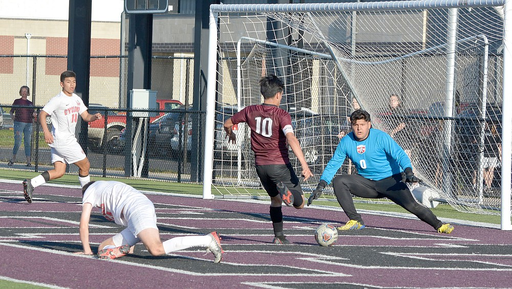 Graham Thomas/Siloam Sunday Siloam Springs senior Franklin Cortez (No. 10) goes one on one with Russellville keeper Noe Jimenez before scoring Siloam Springs' second goal in a 2-0 victory on Friday at Panther Stadium.