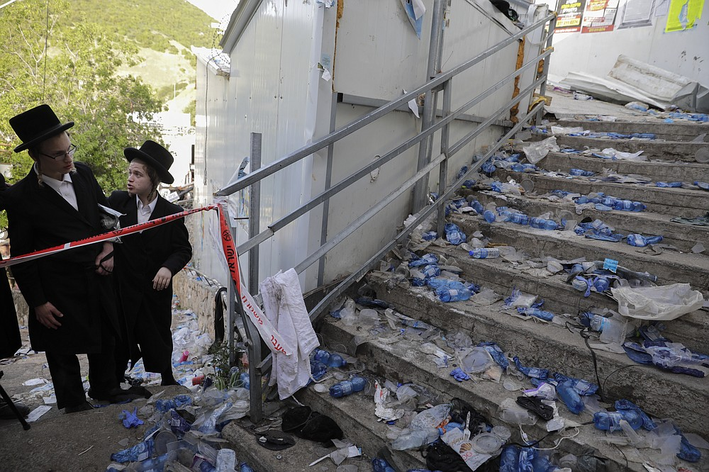 Ultra Orthodox Jews look at the scene where fatalities were reported among the thousands of ultra-Orthodox Jews during Lag BaOmer festival at Mt. Meron in northern Israel, Friday, April 30, 2021. A stampede at a religious festival attended by tens of thousands of ultra-Orthodox Jews in northern Israel killed dozens of people and injured more than 100 others early Friday, medical officials said, in one of the country's deadliest civilian disasters. (AP Photo/Sebastian Scheiner)