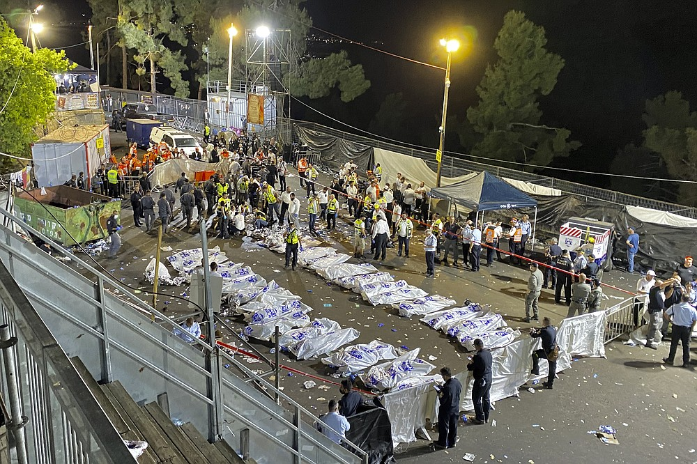 Israeli security officials and rescuers stand around the bodies of victims who died during a Lag Ba'Omer celebrations at Mt. Meron in northern Israel, Friday, April 30, 2021. The director of an Israeli ambulance service has confirmed that nearly 40 people died in a stampede at a religious festival in northern Israel. (Ishay Jerusalemite/Behadrei Haredim via AP)