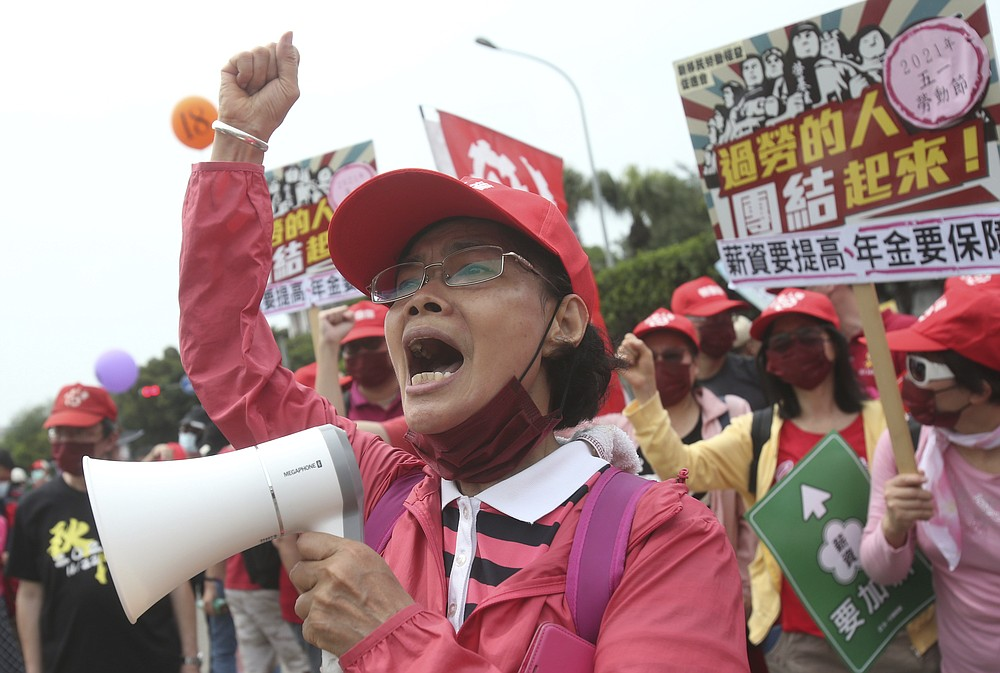 Taiwanese workers shout and hold slogans during a May Day rally in Taipei, Taiwan, Saturday, May 1, 2021. Thousands of protesters from different labor groups protest on the street to ask for increasing salary and securing annuity. (AP Photo/Chiang Ying-ying)